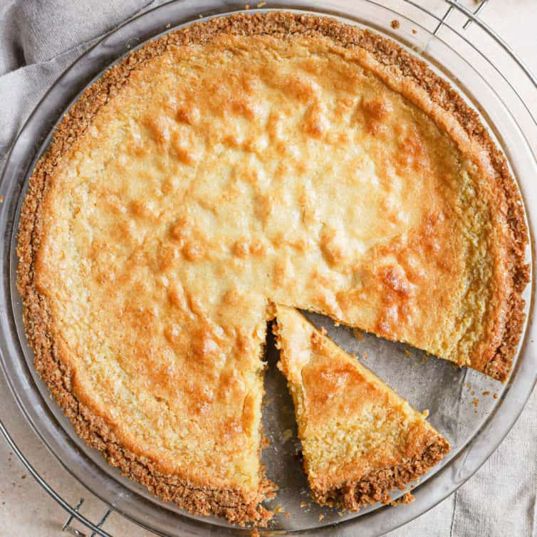 A square photo of a crack pie with a slice cut in the pan in the bottom right side of the pie.