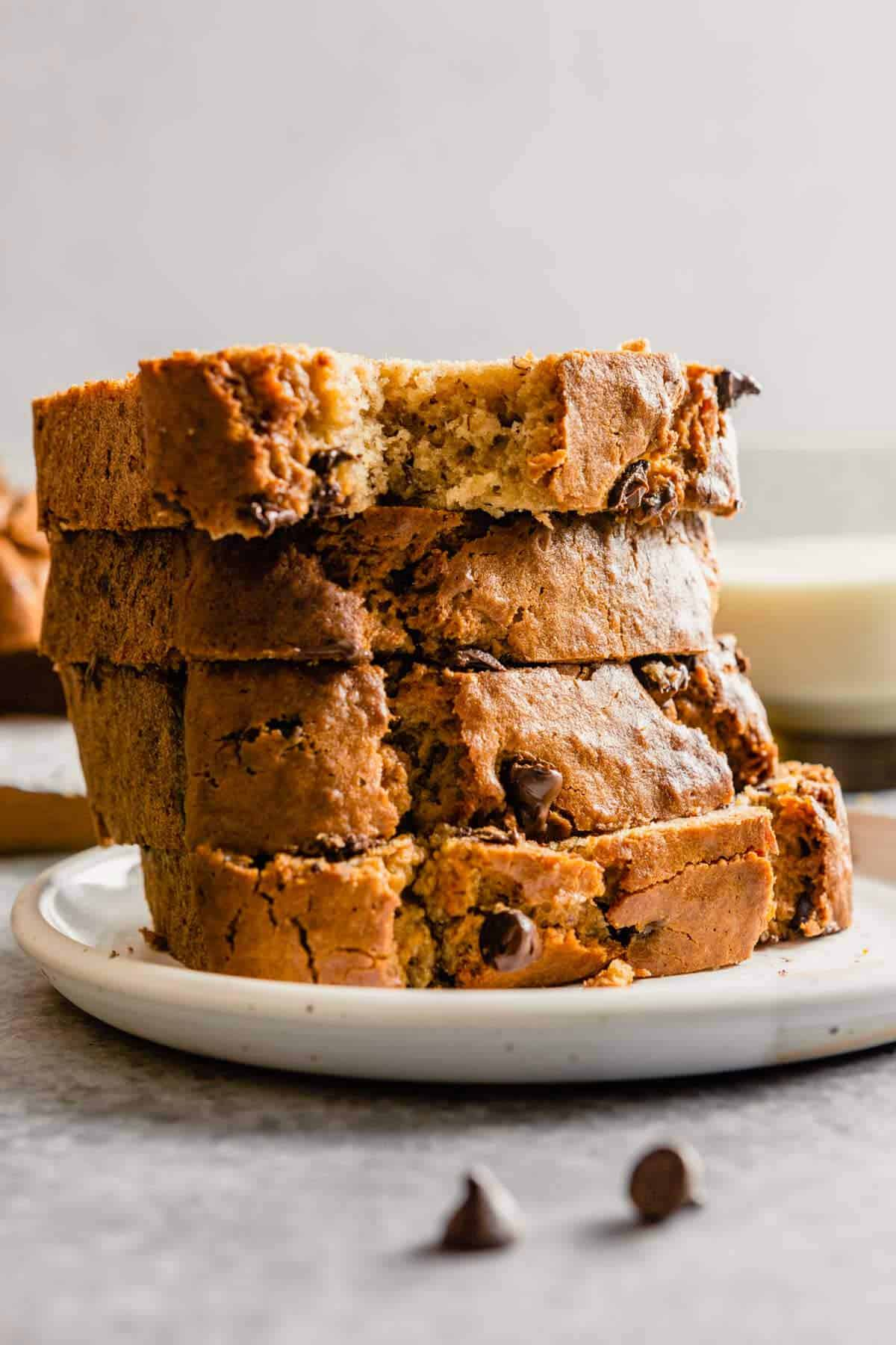 A stack of slices of peanut butter banana bread on a white plate.