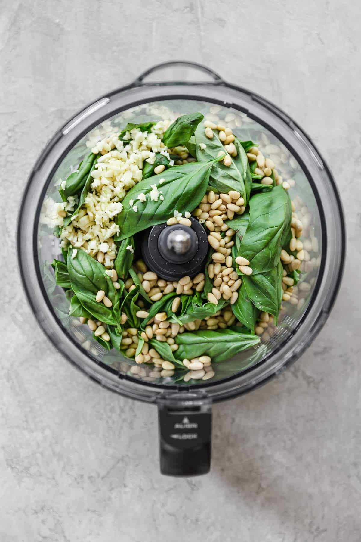 A top down photo of a food processor with the ingredients for pesto in the base.