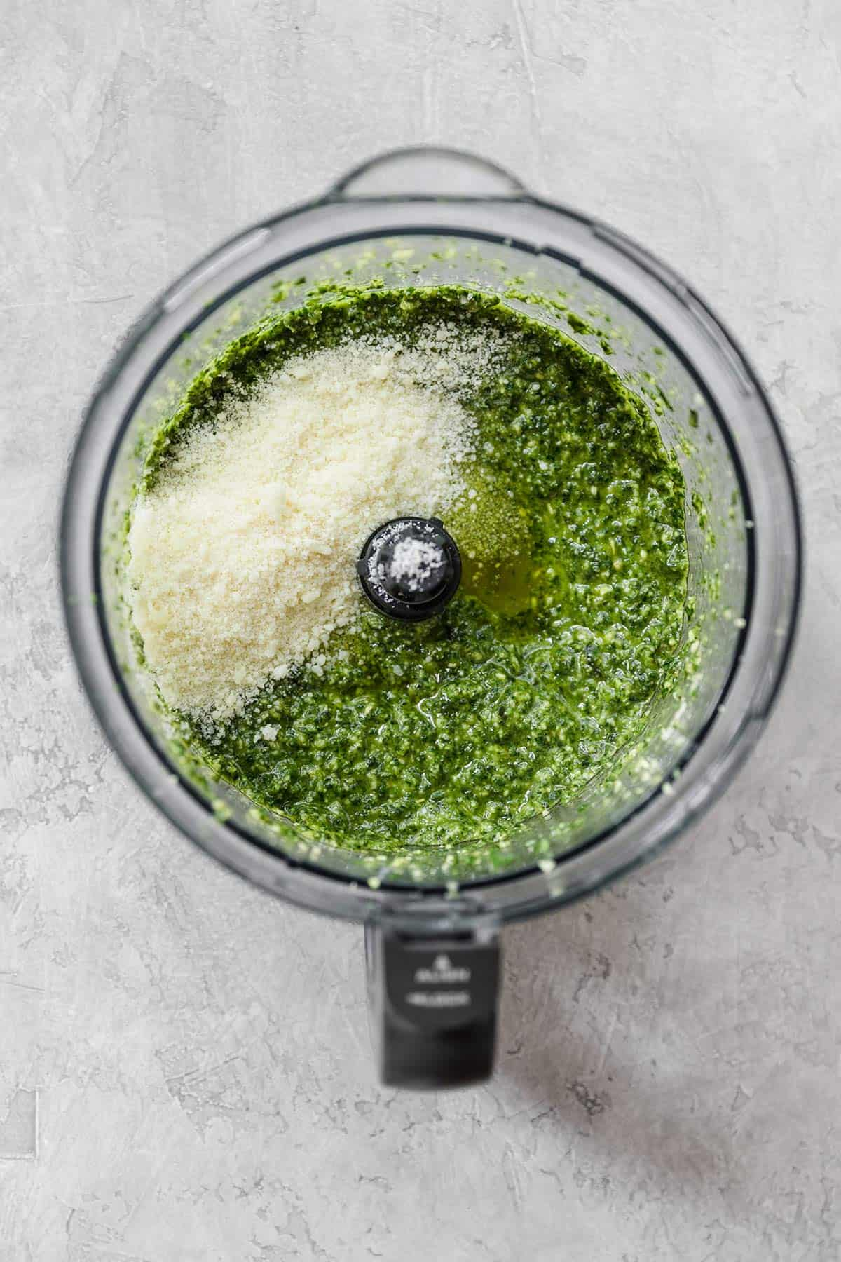 Pesto in a food processor with cheese in the top right section before pulsing.