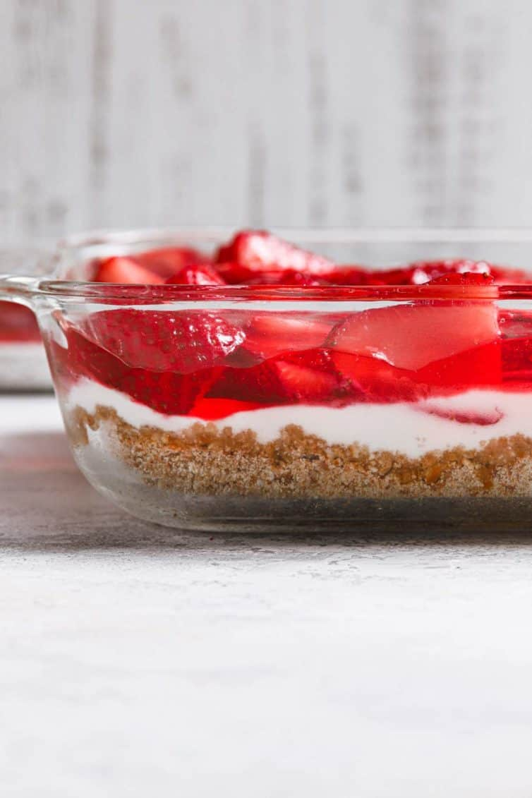 A glass baking dish with strawberry pretzel salad showing the layers in the salad.