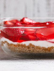 A glass baking dish with strawberry pretzel salad layers.