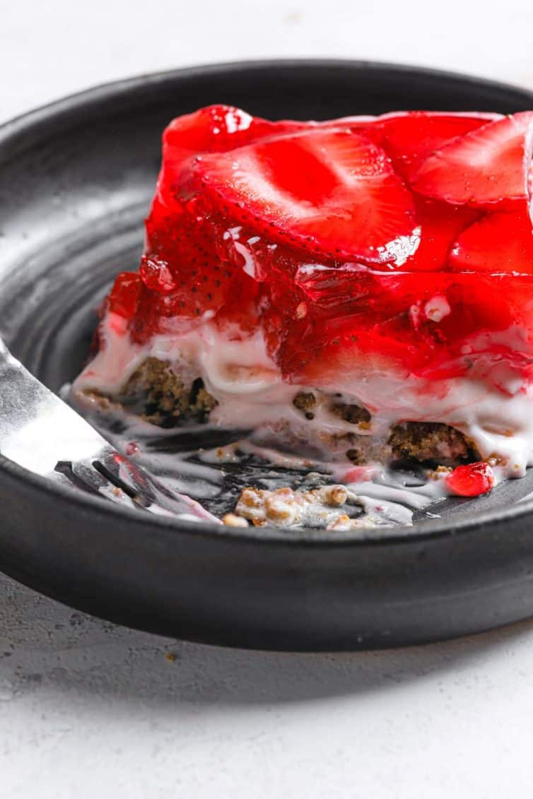A dark grey plate with a slice of strawberry pretzel salad with a fork on the front left of the plate.