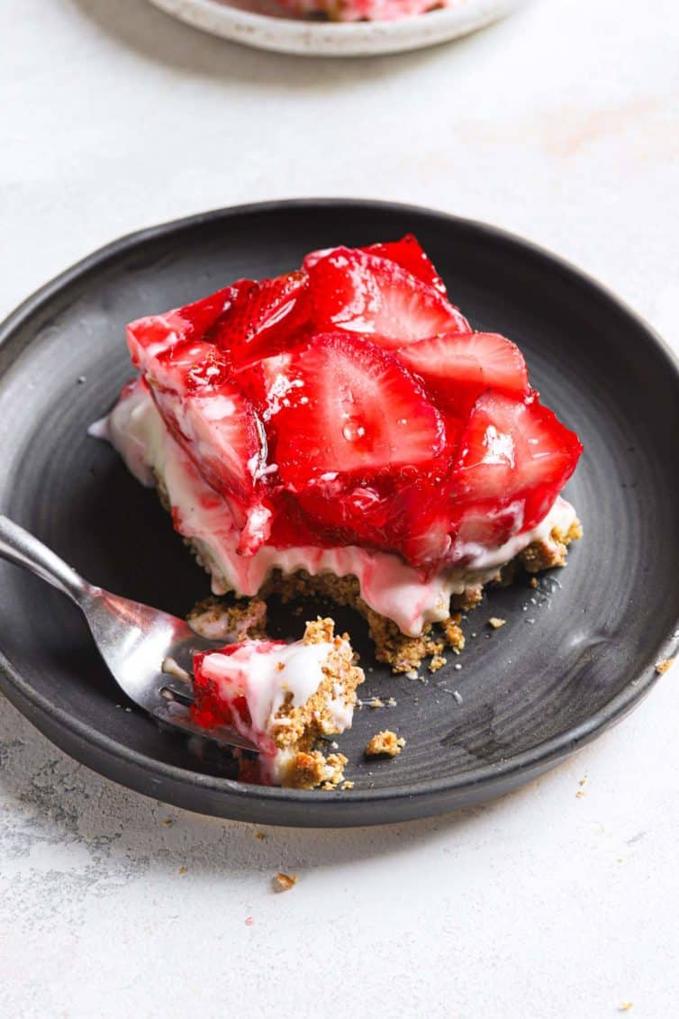 Top down photo of strawberry pretzel salad slice with a fork topped with a bite of the salad.
