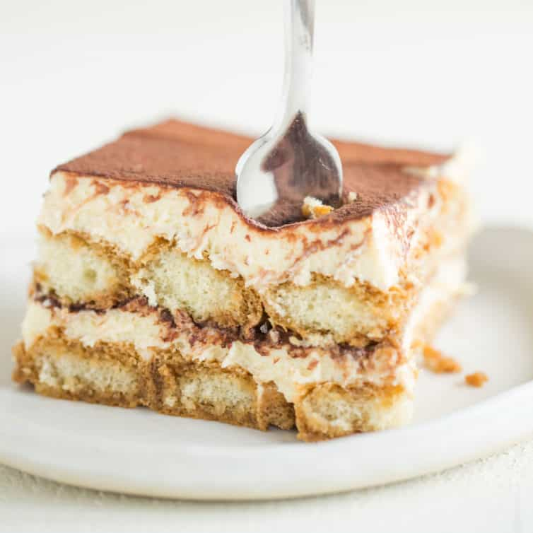 A white plate with a square slice of tiramisu and a fork in the front right corner.
