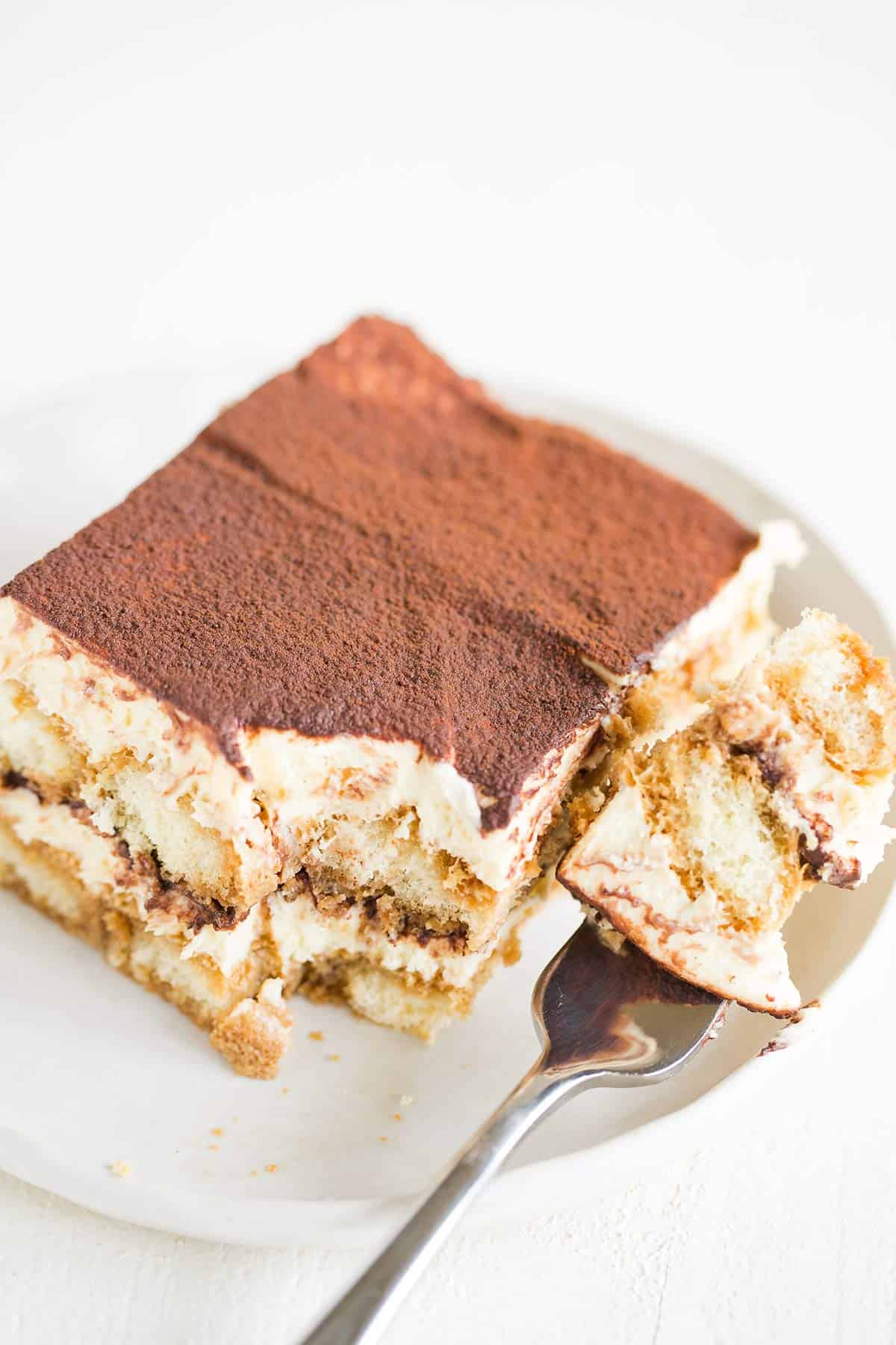 A square slice of tiramisu on a white rimmed plate with a fork full of tiramisu to the right.