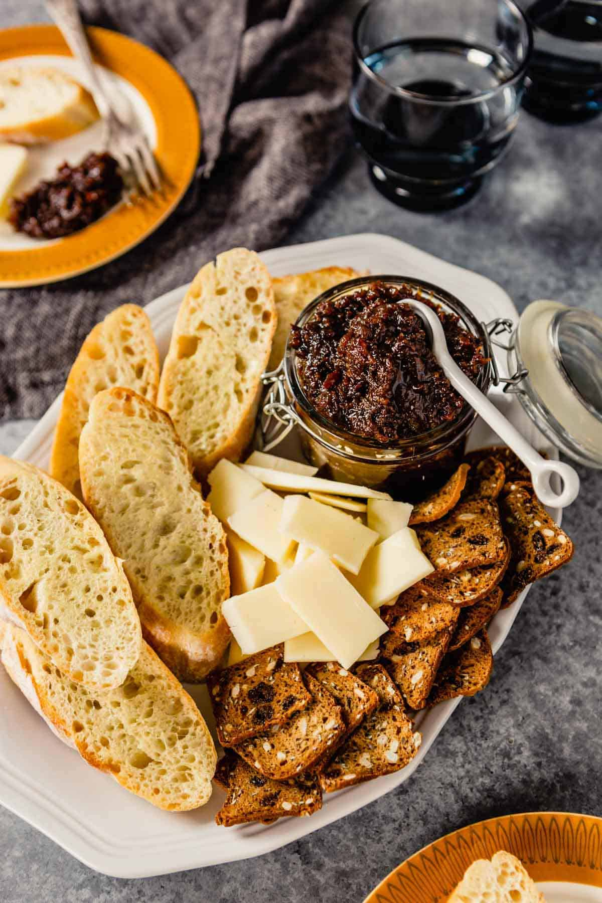 A platter with a jar of bacon jam in the top right and cheese, crackers, and bread on the platter.
