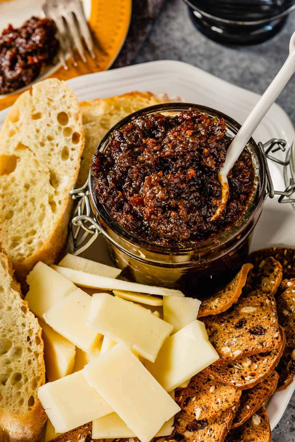 A glass jar of bacon jam with a spoon on a white plate with cheese in front and crackers to the left.