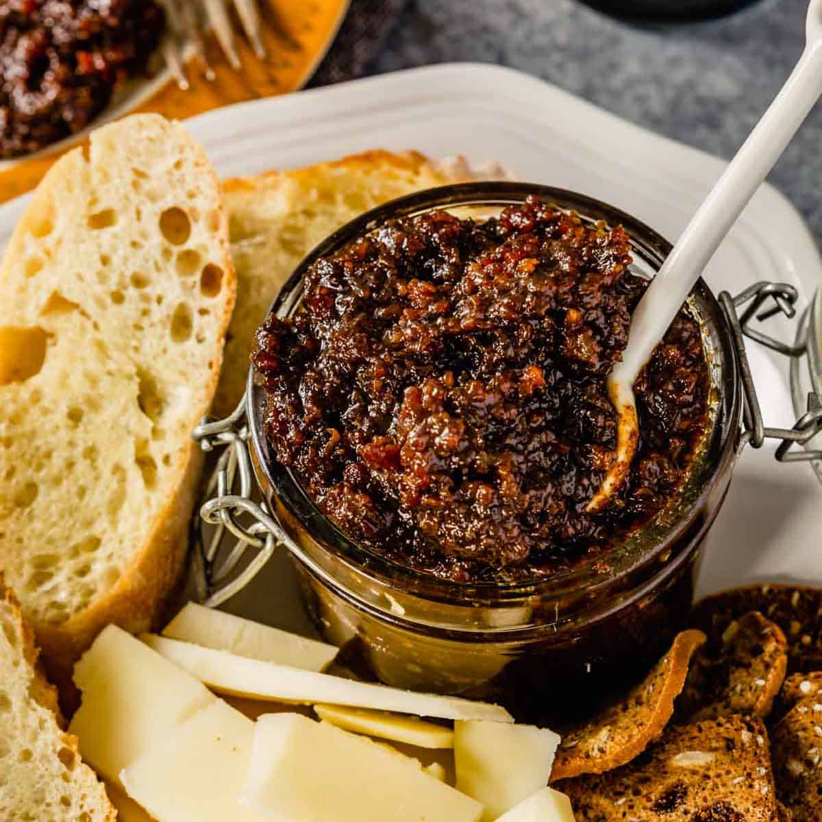 A glass jar of bacon jam on a white plate with a white spoon scooping the jam.