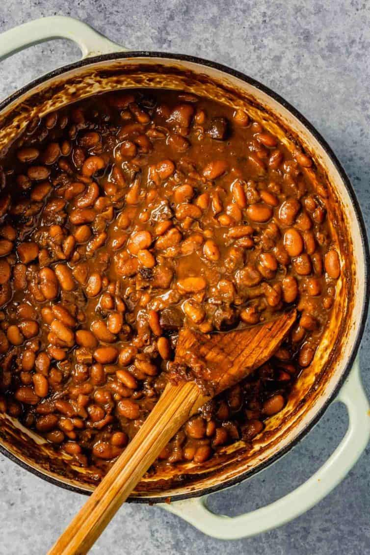 A white dutch oven with Boston baked beans and a wooden spoon to the left.