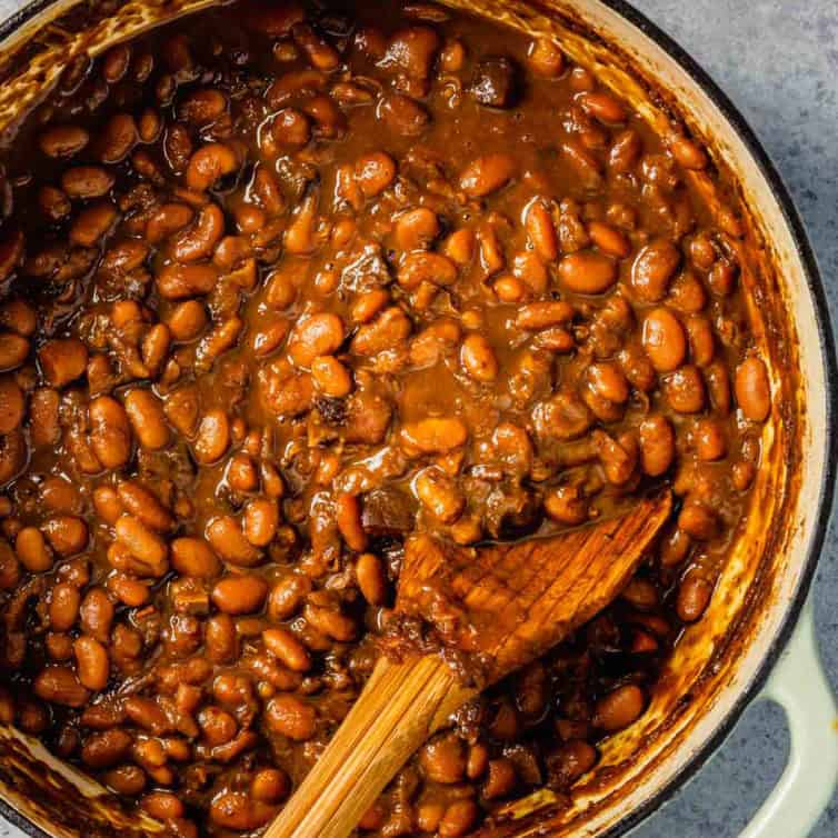 A top down photo of Boston baked beans in a dutch oven with a wooden spoon.