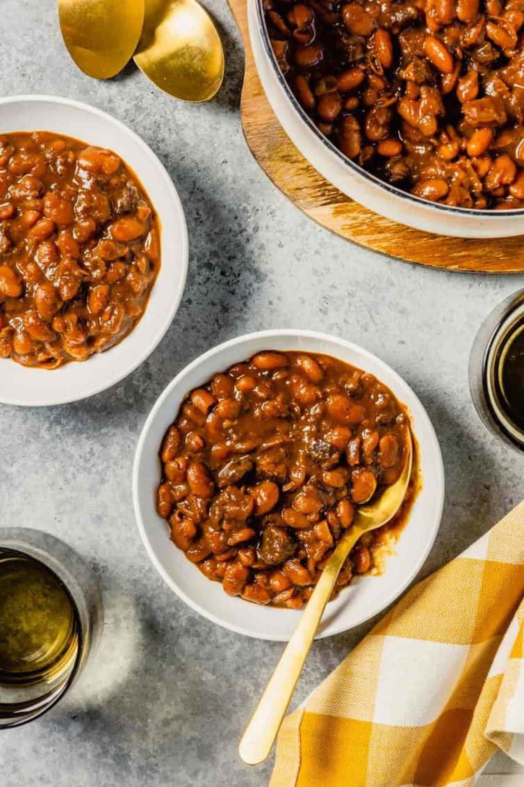 A white bowl with baked beans and a spoon on a grey counter with beans in another white bowl to the top left and top right.
