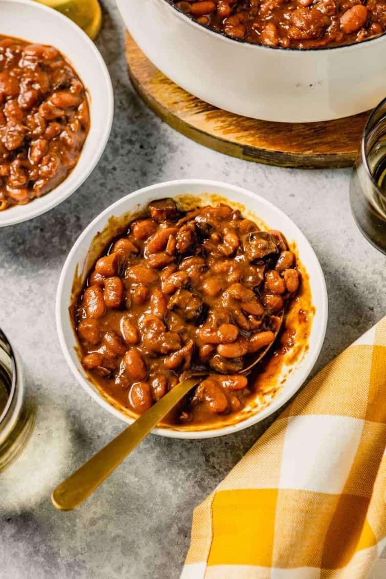 A white bowl with baked beans and a yellow and white buffalo check towel to the bottom left.
