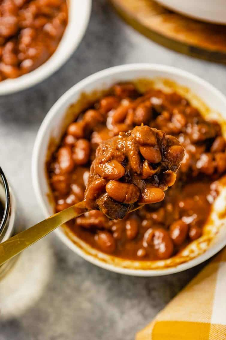 A spoon with a scoop of Boston baked beans over a white bowl.