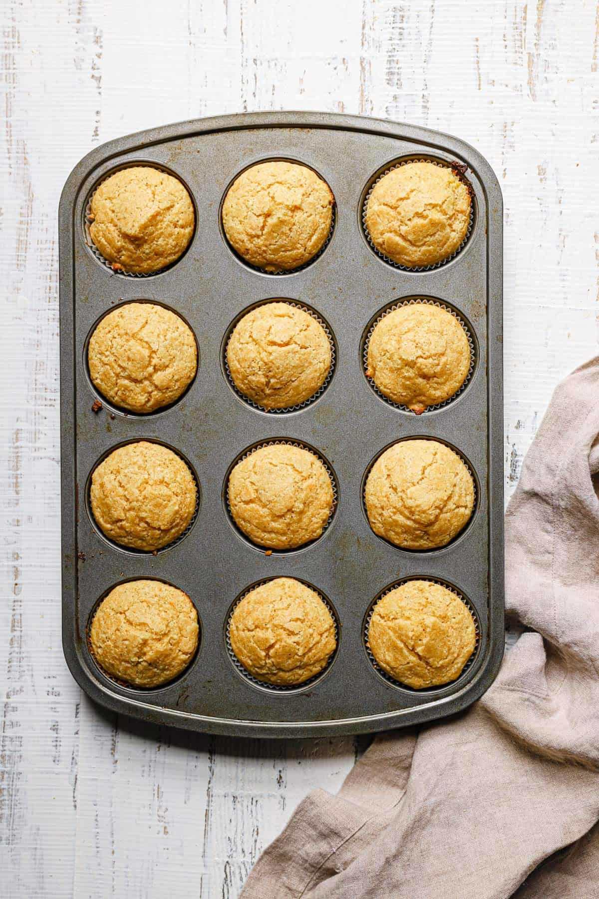 A silver muffin tin with cornbread muffins on a white counter with a light beige dish towel to the left.