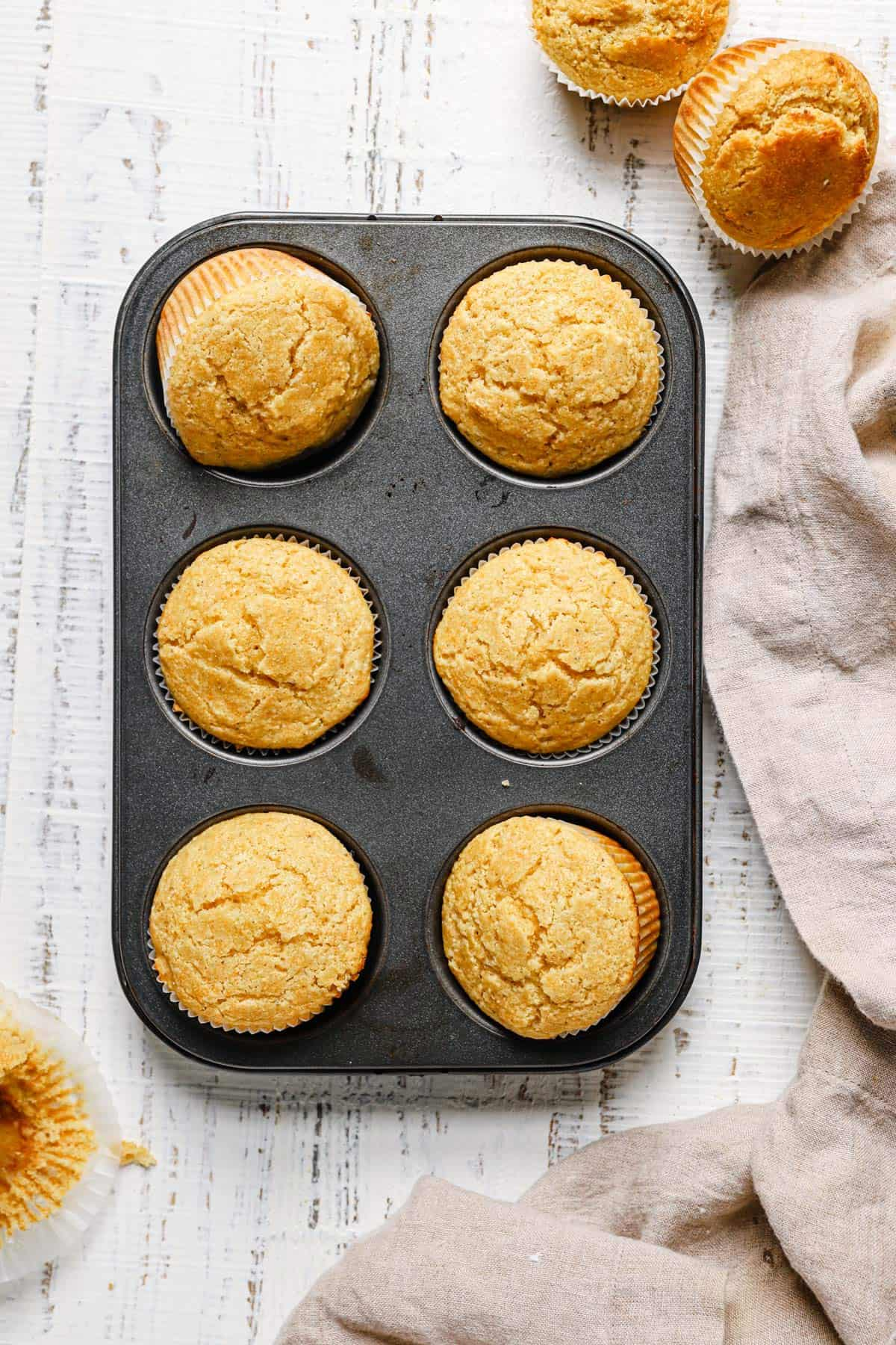 Top down photo of a muffin tin with 6 cornbread muffins on a white counter with two muffins in the top right and a towel in the bottom right.