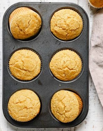 A close up of a non-stick muffin tin with cornbread muffins on a white counter with a light beige towel to the right.