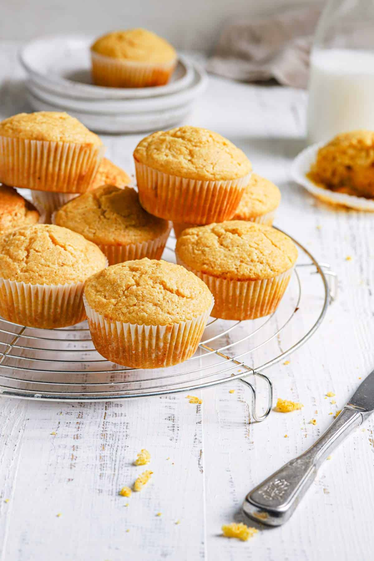 A wire cooling rack with cornbread muffins in a stack with a stack of plates in the back topped with a cornbread muffin and a milk jug to the right.