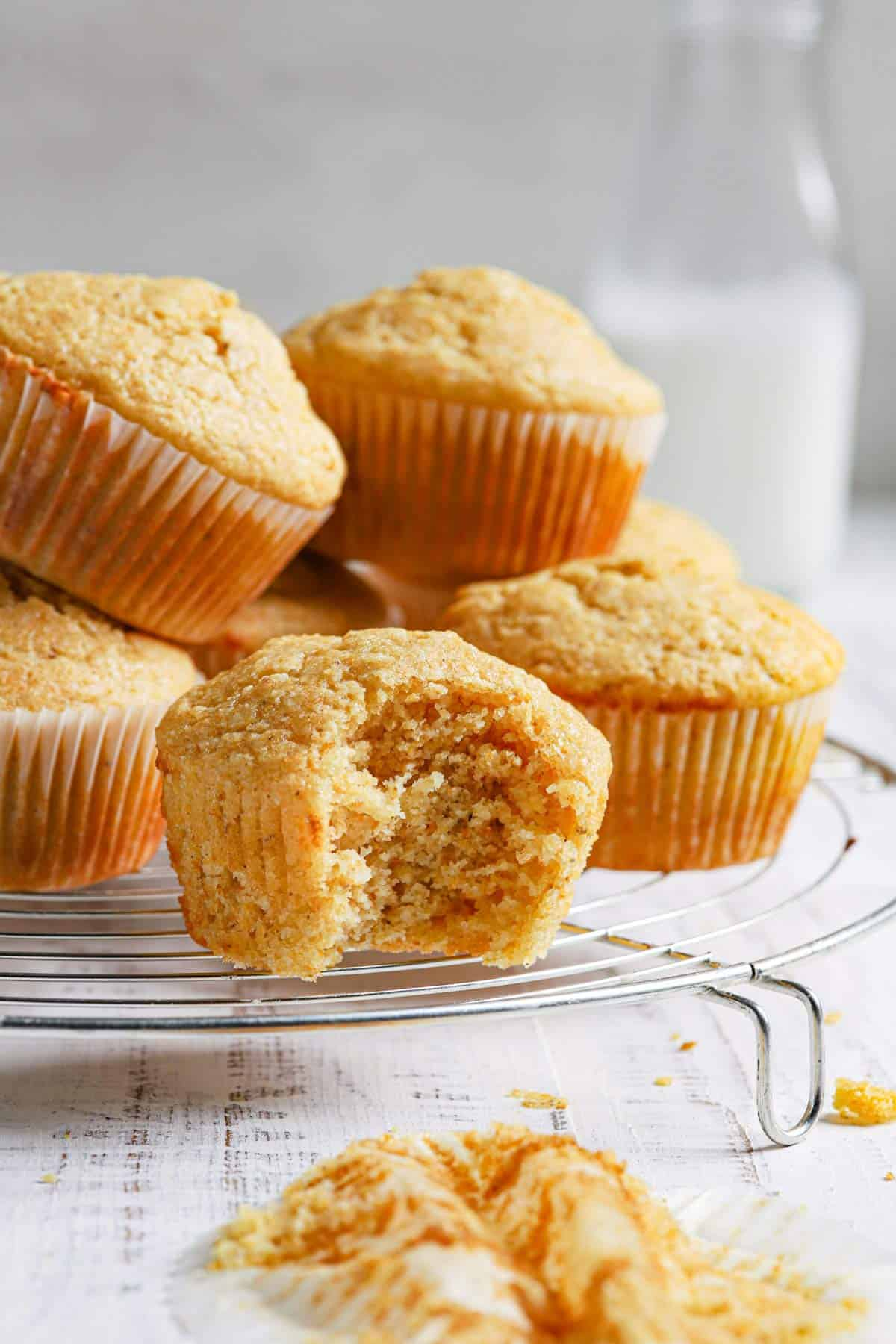 Fresh cornbread muffins on a wire rack with the front muffin missing a bite and a jug of milk in the back.