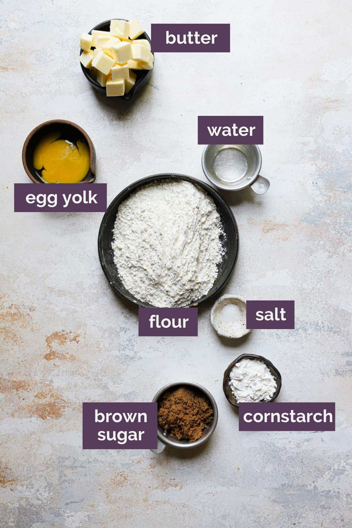 The ingredients for the shortbread crust in bowls with purple labels naming each ingredient.