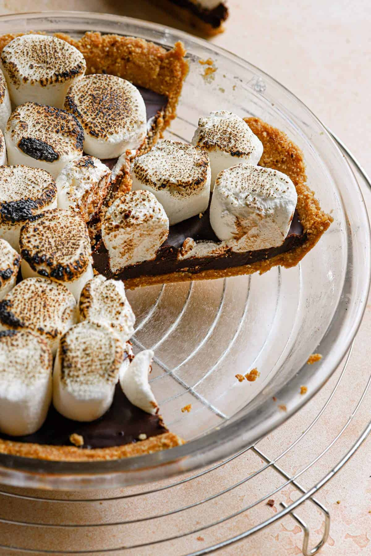 A glass pie plate with a s'mores pie slice from the side to show the layers of the pie.