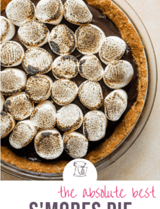 A s'mores pie on a peach counter with the words The Absolute Best S'mores Pie at the bottom.