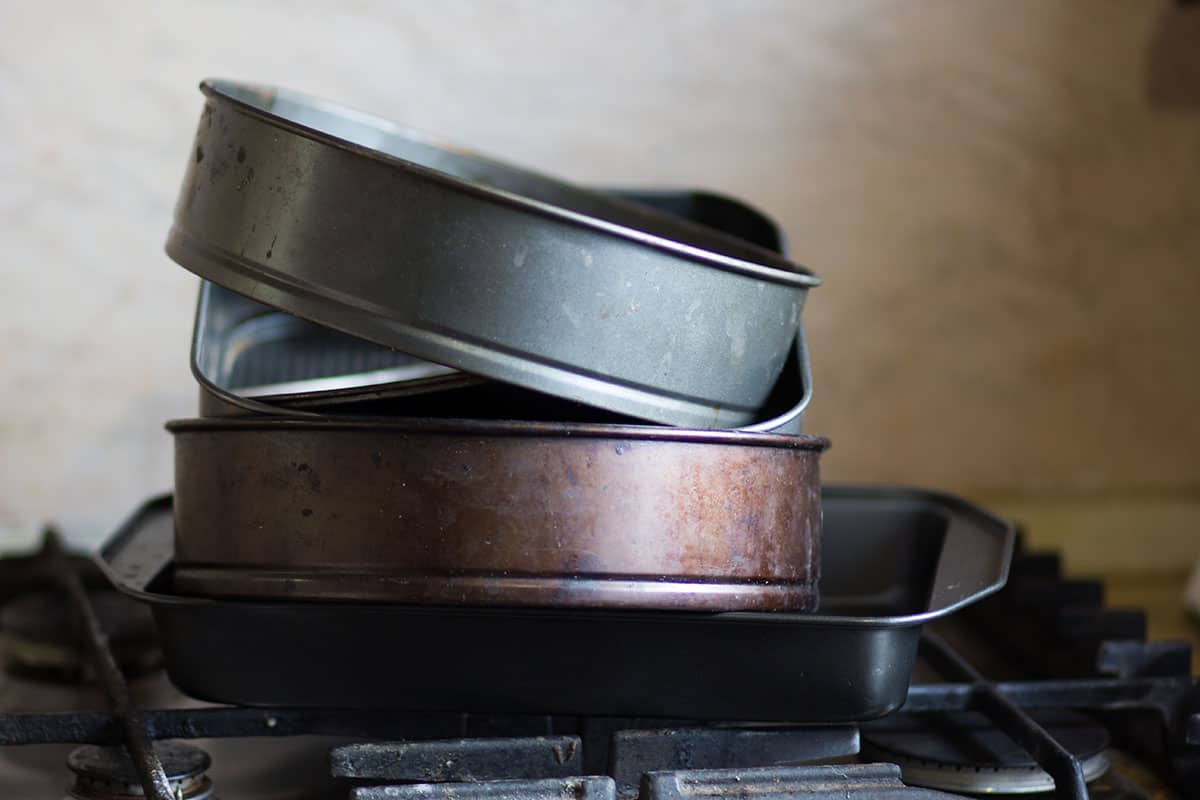 Baking pans stacked on a stove burner.