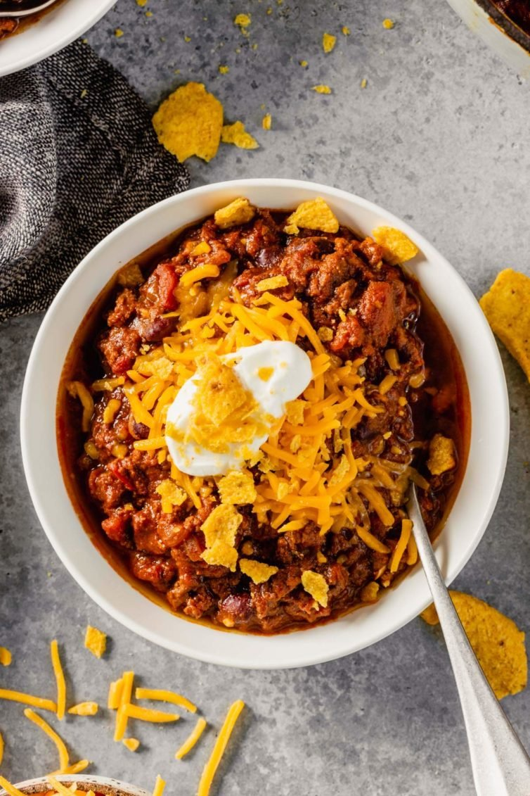 A white bowl filled with beef chili and topped with cheddar cheese, sour cream, and a silver spoon on the right.