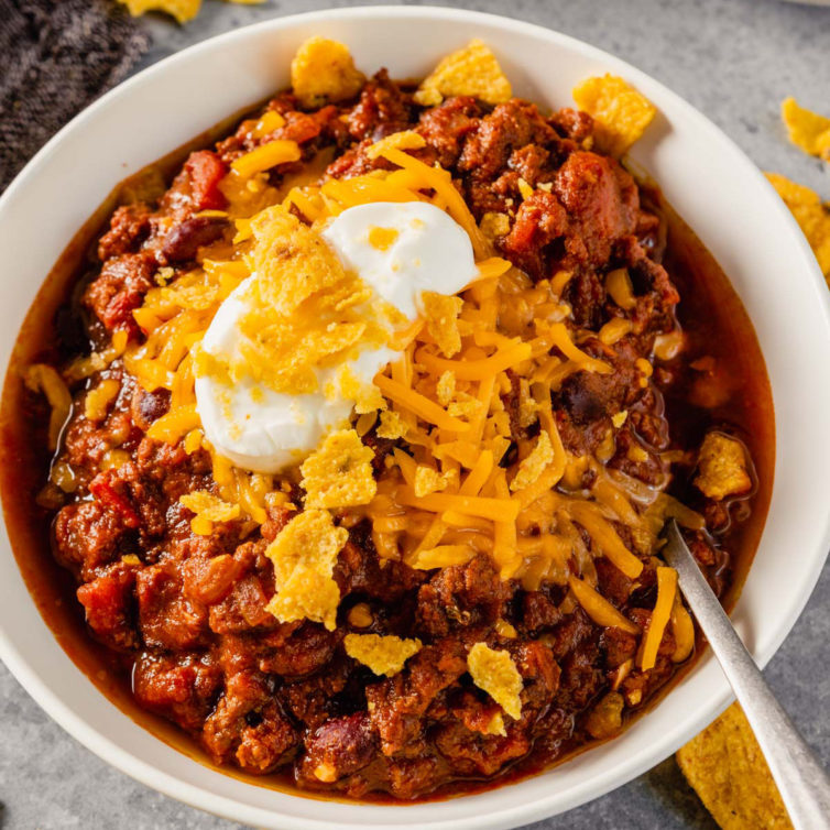 A white bowl with fresh ground beef chili topped with cheese, sour cream, and crushed Fritos with a spoon in the right side of the bowl.