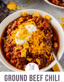 A white bowl of ground beef chili topped with cheese and sour cream with the words Ground Beef Chili the best ever at the bottom.