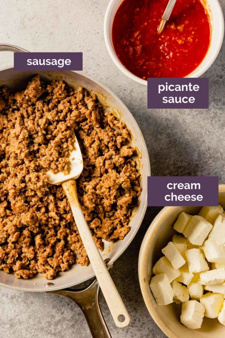 Three bowls on a grey counter with ingredients for sausage dip labeled with purple text boxes.