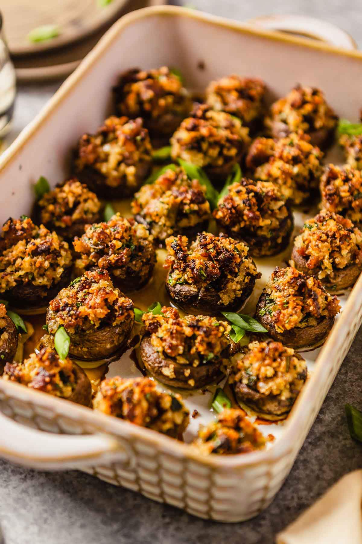 A rectangular baking dish with handles filled with sausage stuffed mushrooms.