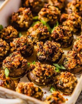 A rimmed baking dish with sausage stuffed mushrooms garnished with green onion.
