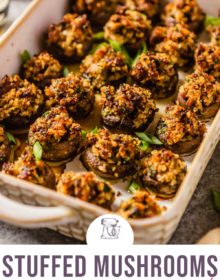 A rimmed baking dish filled with sausage stuffed mushrooms and the words Stuffed Mushrooms sausage and mascarpone at the bottom in pink.