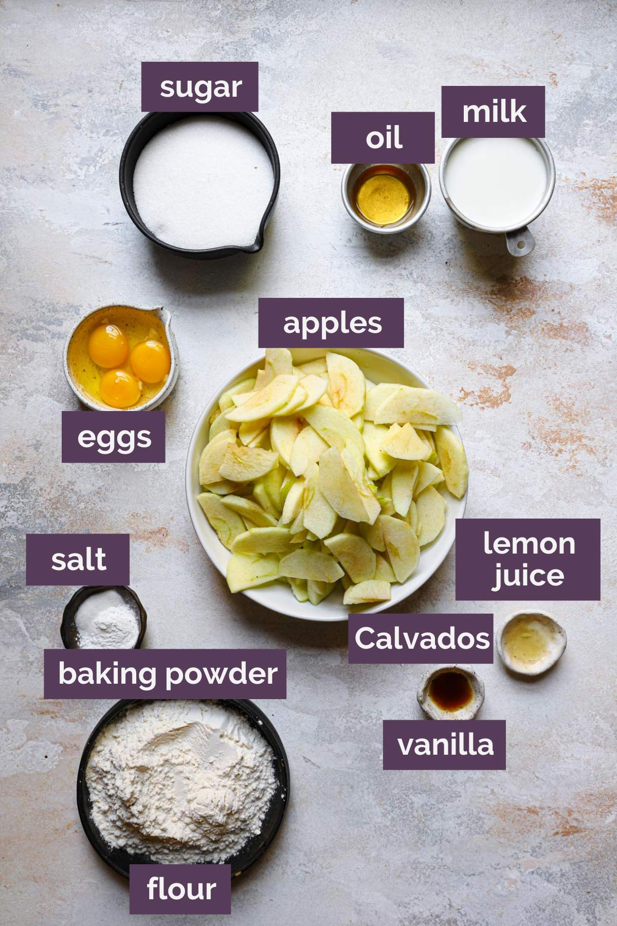 Ingredients for French apple cake prepped on a counter and labeled.