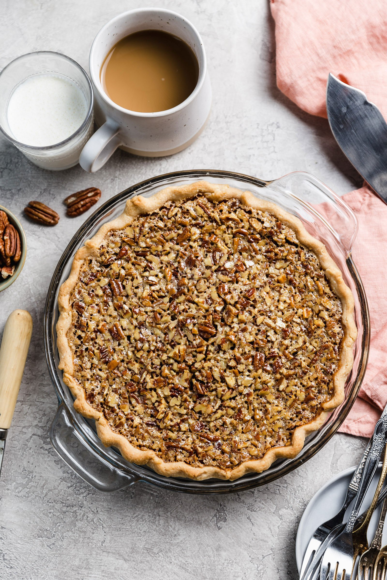 Overhead photo of baked pecan pie with forks and a cup of coffee next to it.