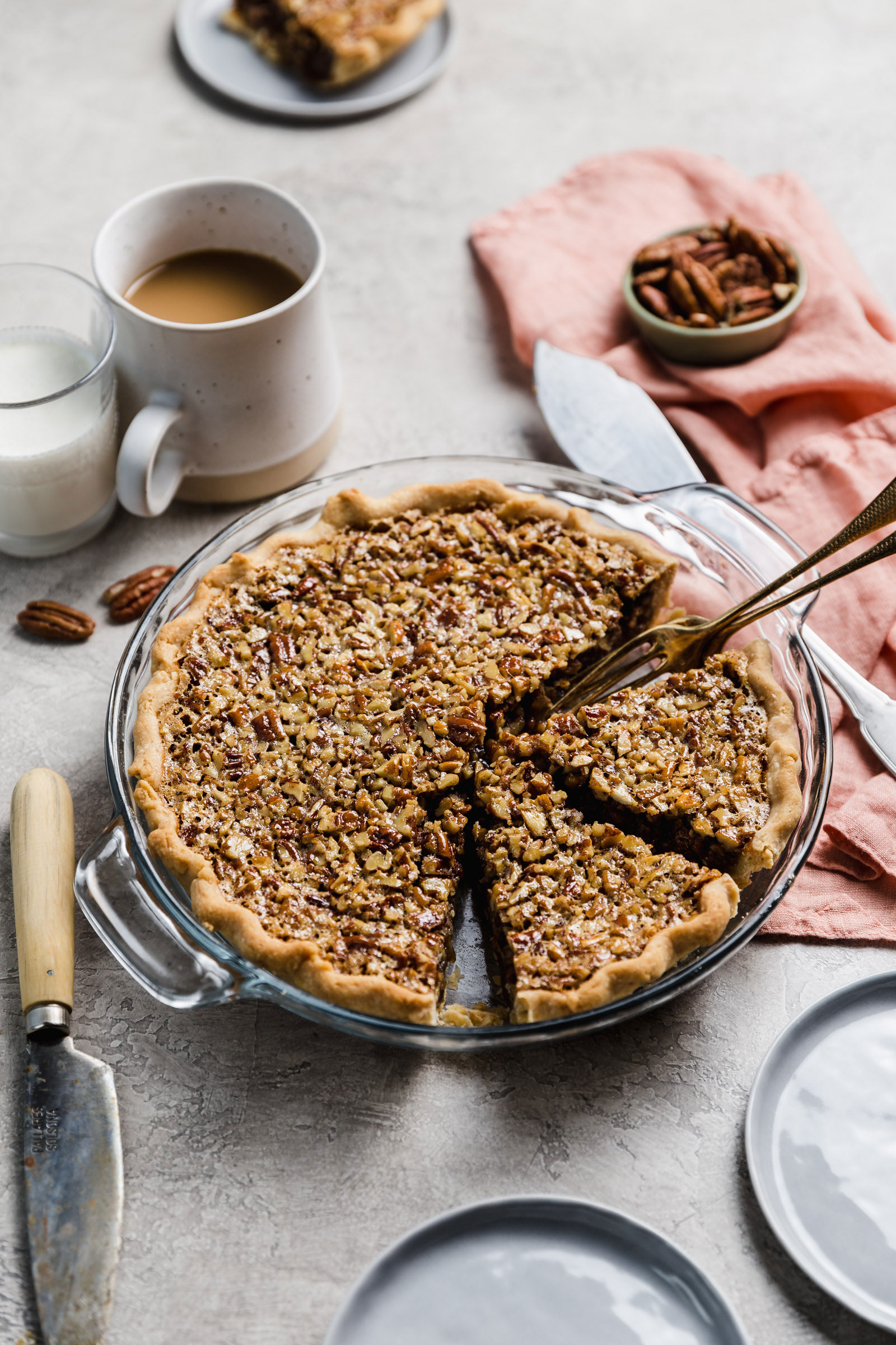 Pecan pie with two slices cut away and two forks resting inside the pie plate.