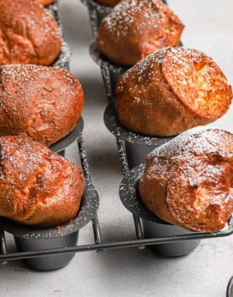 Golden brown baked breakfast popovers in a grey popover baking pan dusted with powdered sugar