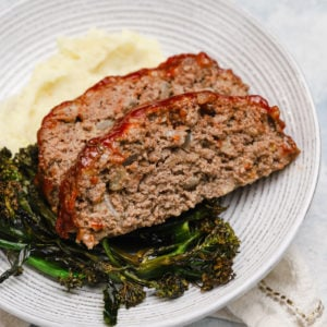 2 slices of meatloaf on a white plate with roasted broccoli and mashed potatoes.