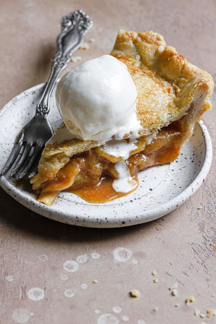 a slice of this salted caramel apple pie served on a stoneware plate with vanilla ice cream