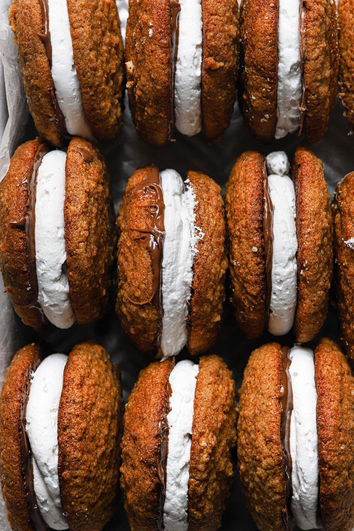 S'mores whoopie pies packed together standing on end with chocolate and marshmallow filling.